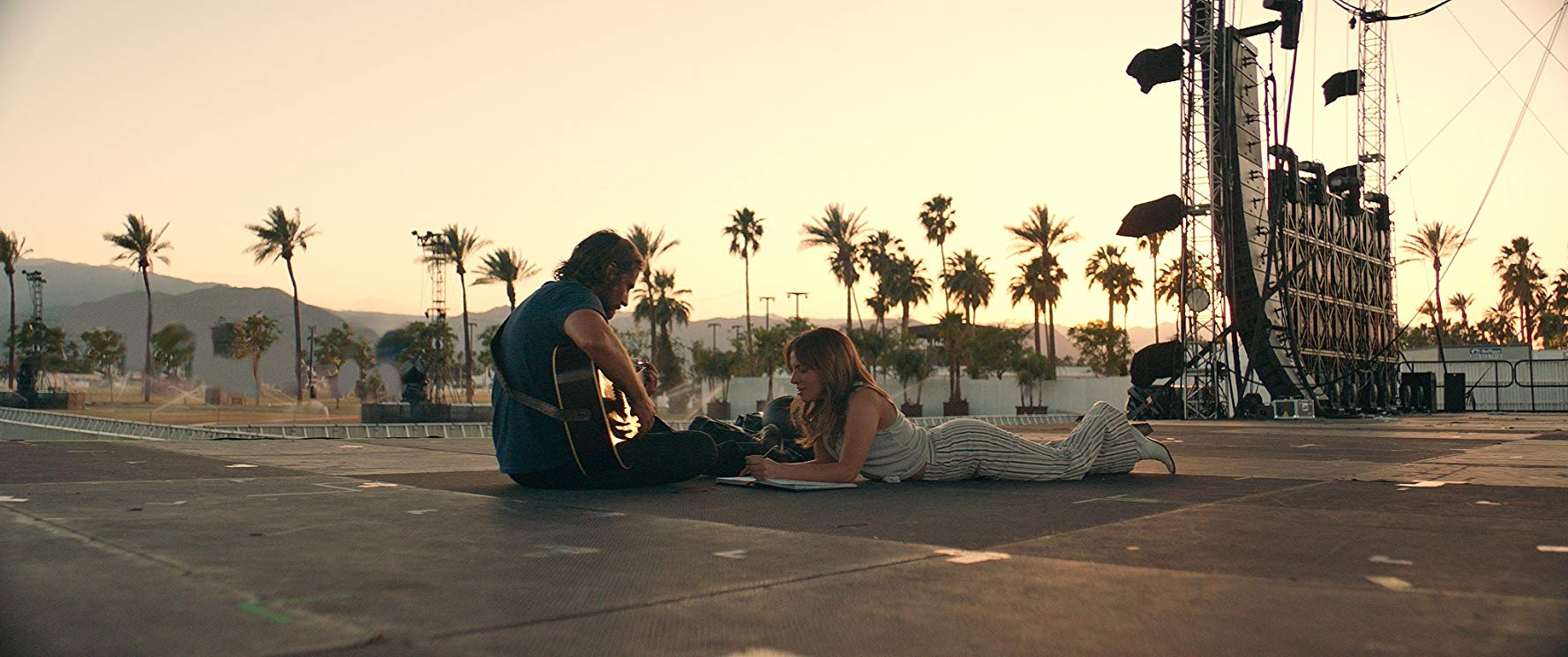 In a still from a scene cut from the original theatrical version of A Star Is Born, Bradley Cooper and Lady Gaga sit on an empty stage together writing music.