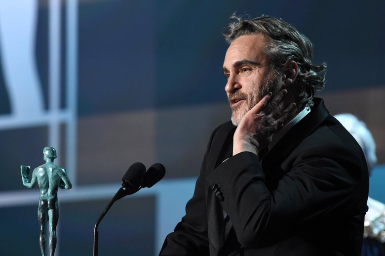 Joaquin Phoenix at a podium with a green statue of a naked man.