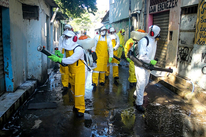 People wearing protective suits and masks and headphones carry vacuums while walking down the aisle of a favela.
