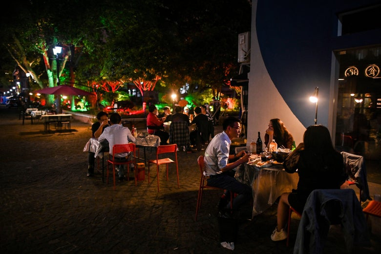 People eat outdoor next to a restaurant in Wuhan, in China's central Hubei province on April 16, 2020. - China has largely brought the coronavirus under control within its borders since the outbreak first emerged in the city of Wuhan late last year. (Photo by Hector RETAMAL / AFP) (Photo by HECTOR RETAMAL/AFP via Getty Images)