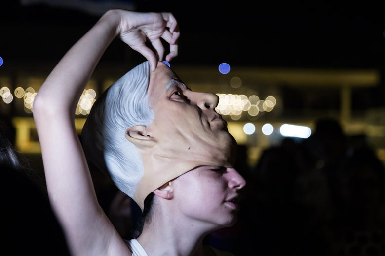 A young woman pulls a mask of Benjamin Netanyahu's face off her head