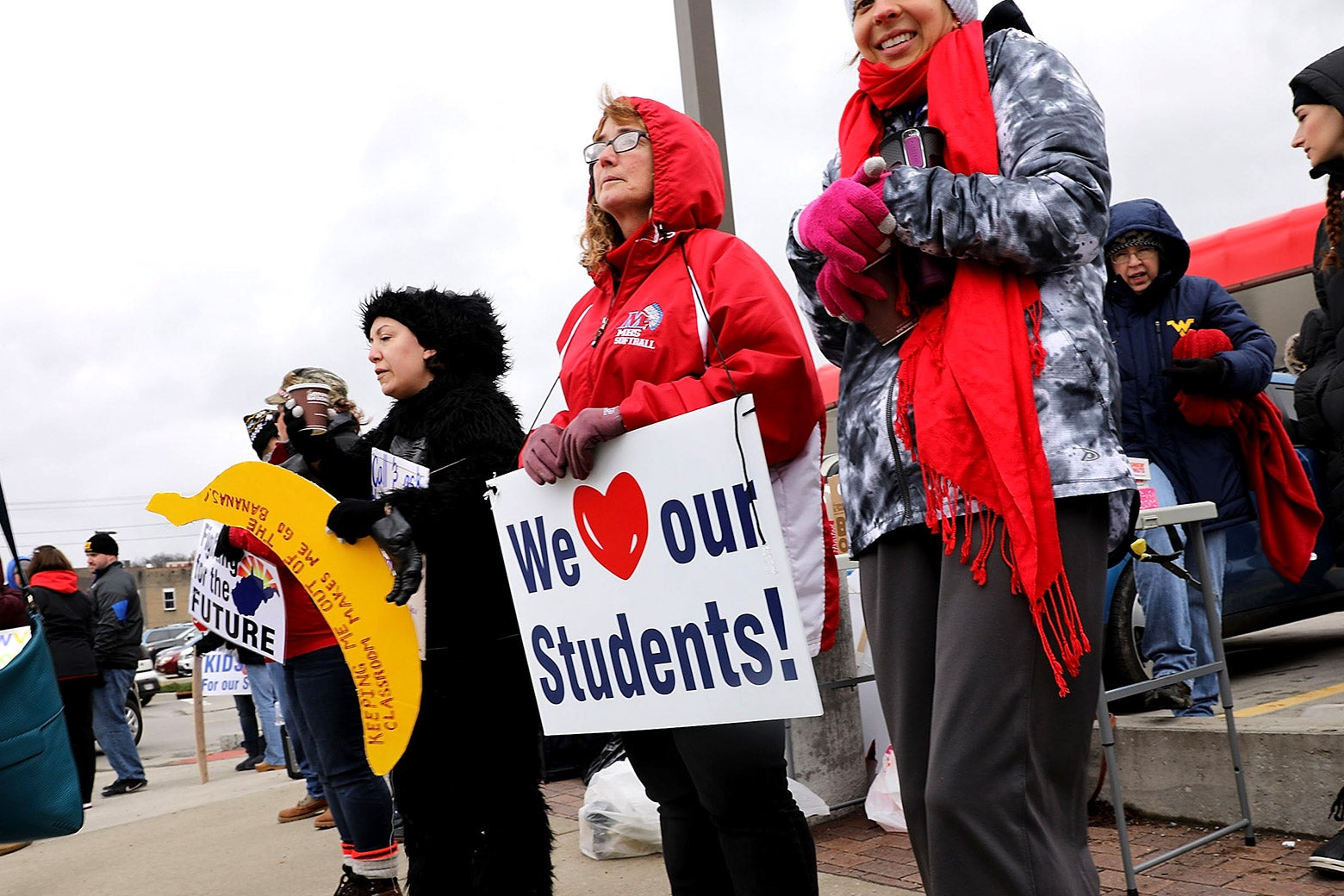 West Virginia teachers, students and supporters hold signs on a Morgantown street as they continue their strike on March 2, 2018 in Morgantown, West Virginia.