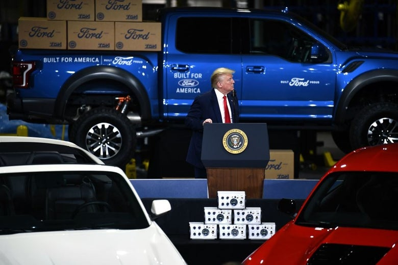 Trump looks to his left from a presidential lectern set up amid cars and trucks.