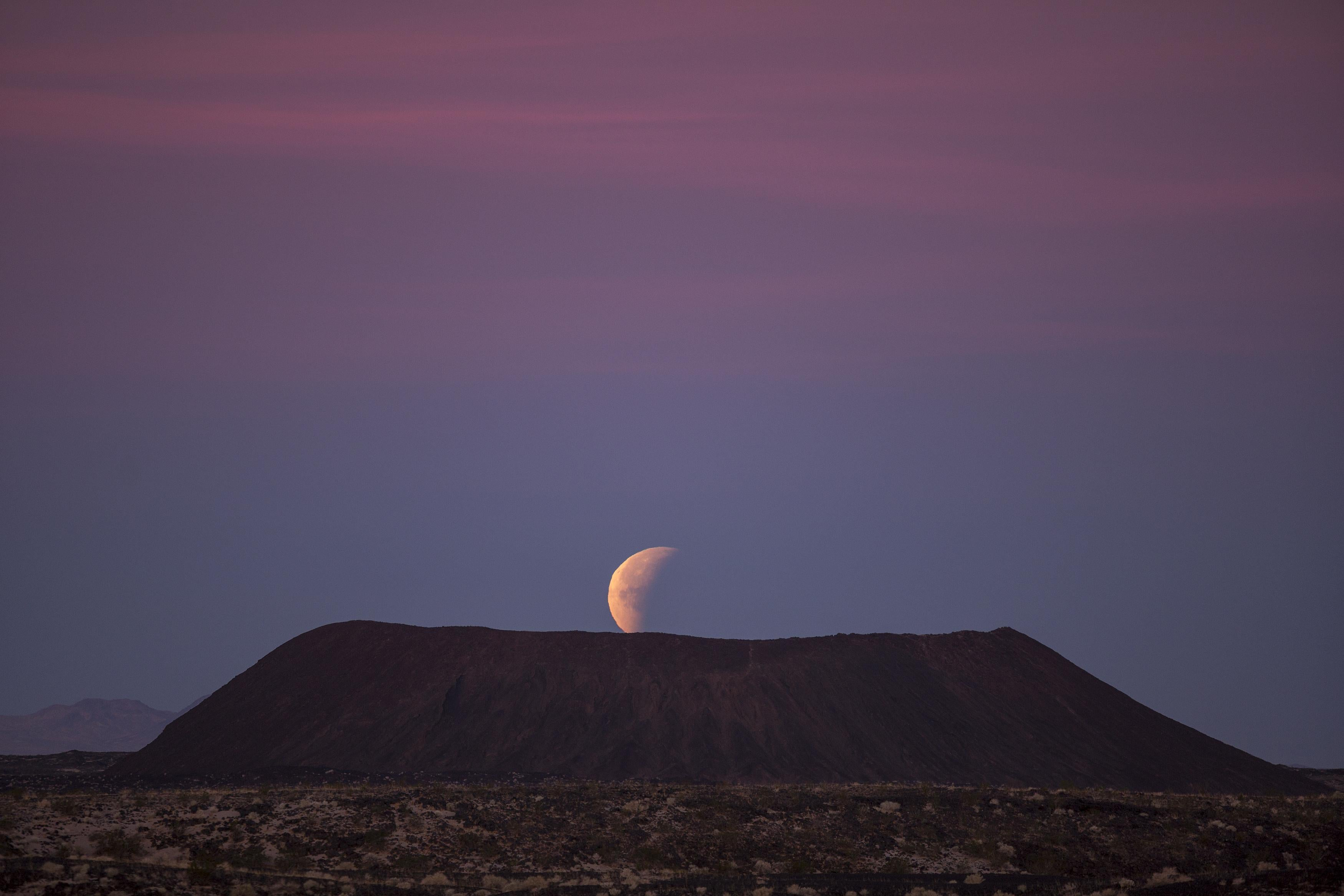 A so-called super blue blood moon sets behind Amboy Crater in the Mojave Desert.