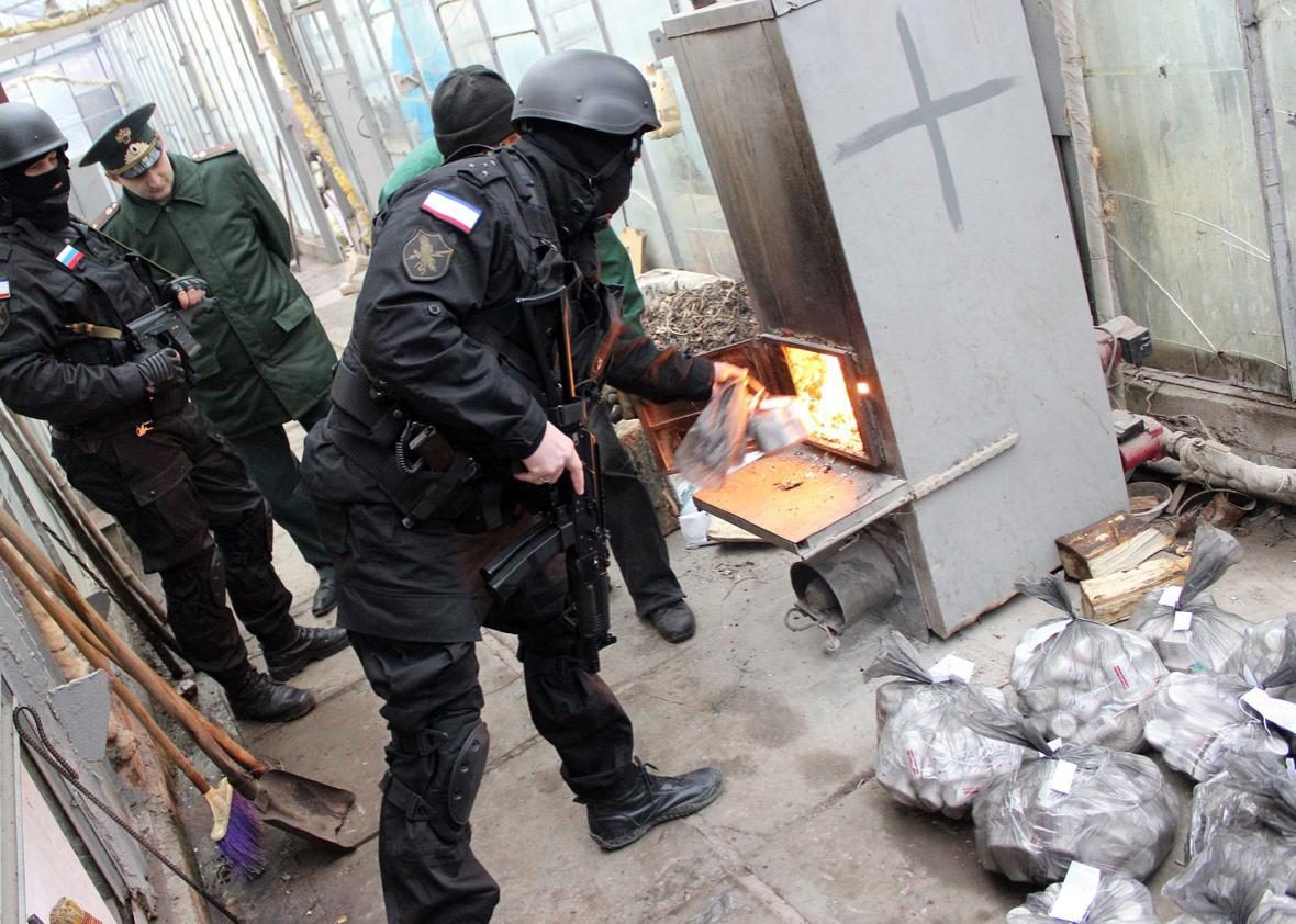 Russian Federal Drug Control Service officers burn bags of synthetic opioid Methadone