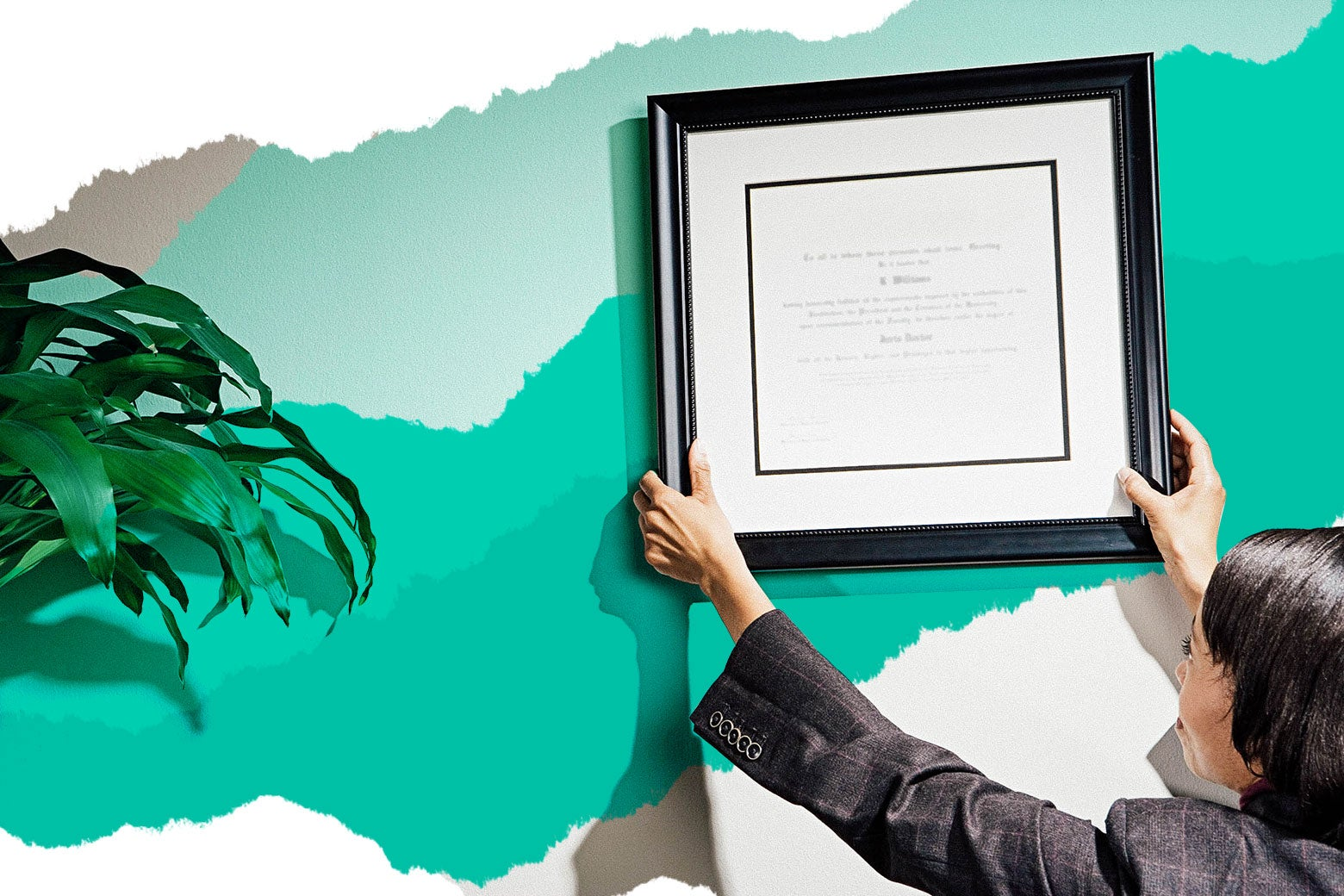 A woman mounts a framed certification on an office wall.