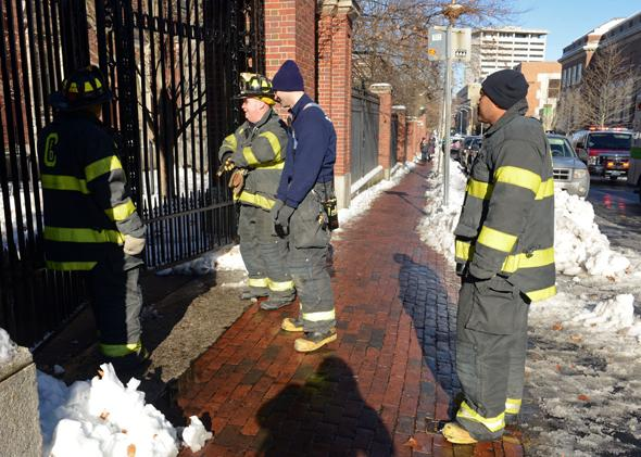 Firefighters check a locked gate on Quincy Street at Harvard University during the bomb scare