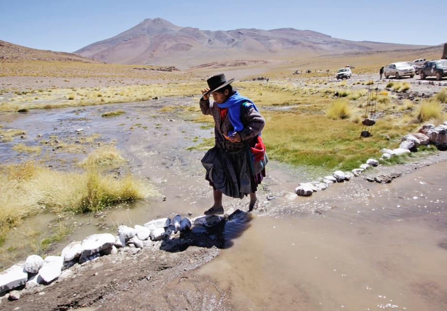 A woman walks past while attending the inauguration of program by Bolivia's President Evo Morales in Silala on the border with Chile, about 497 miles south of La Paz, Bolivia, March 28, 2013.