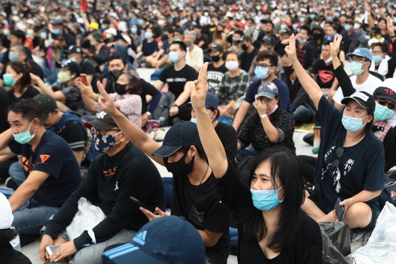 A large crowd of protesters sitting on the ground outside, wearing black T-shirts and masks. Many raise their right arms, holding up three fingers in the Hunger Games salute.