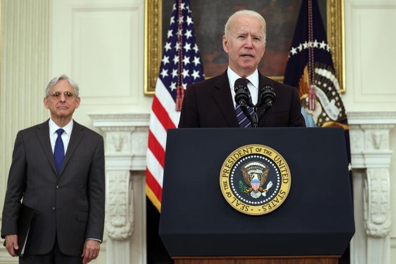 Biden speaks at a podium with Garland standing behind him