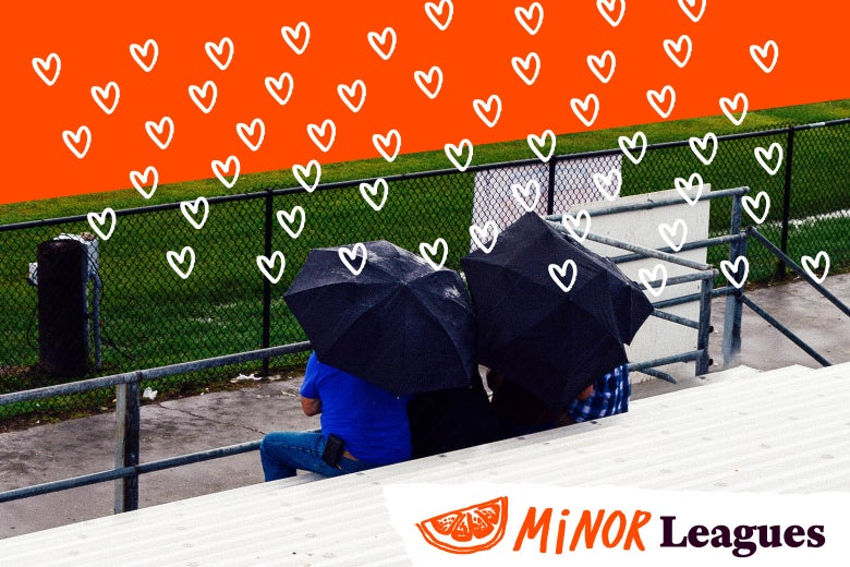 Parents on the bleachers under umbrellas as hearts rain down.