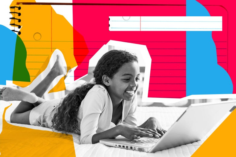 A child lies on her bed, typing at a laptop. A notebook can be seen in the background