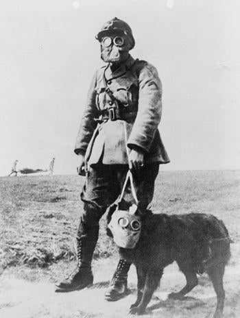 A French sergeant and a dog, both wearing gas masks, on their way to the front line.