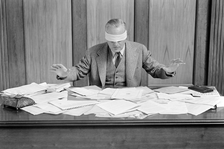 Blindfolded man sitting at a desk covered in papers.
