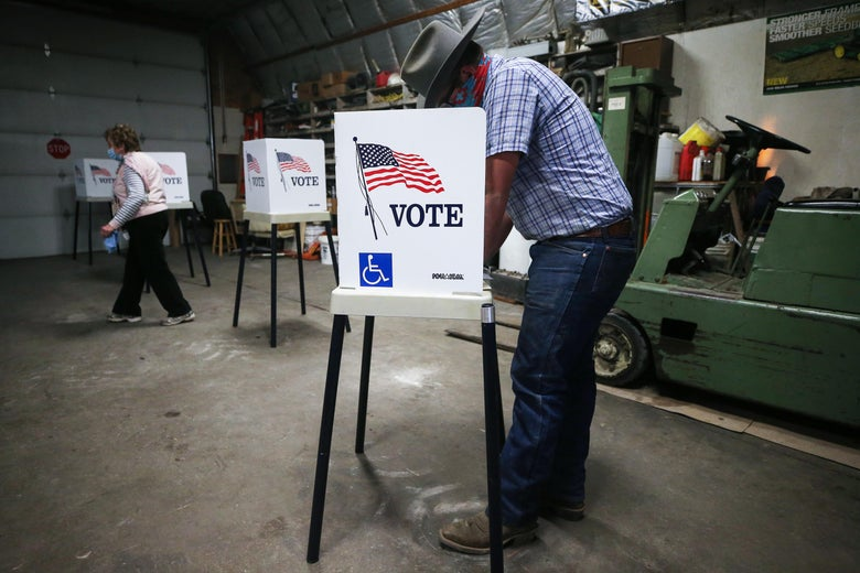 A voter marks his ballot in a voting booth inside a shed