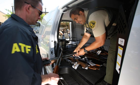 ATF officers load some of about 125 weapons confiscated in a gang takedown