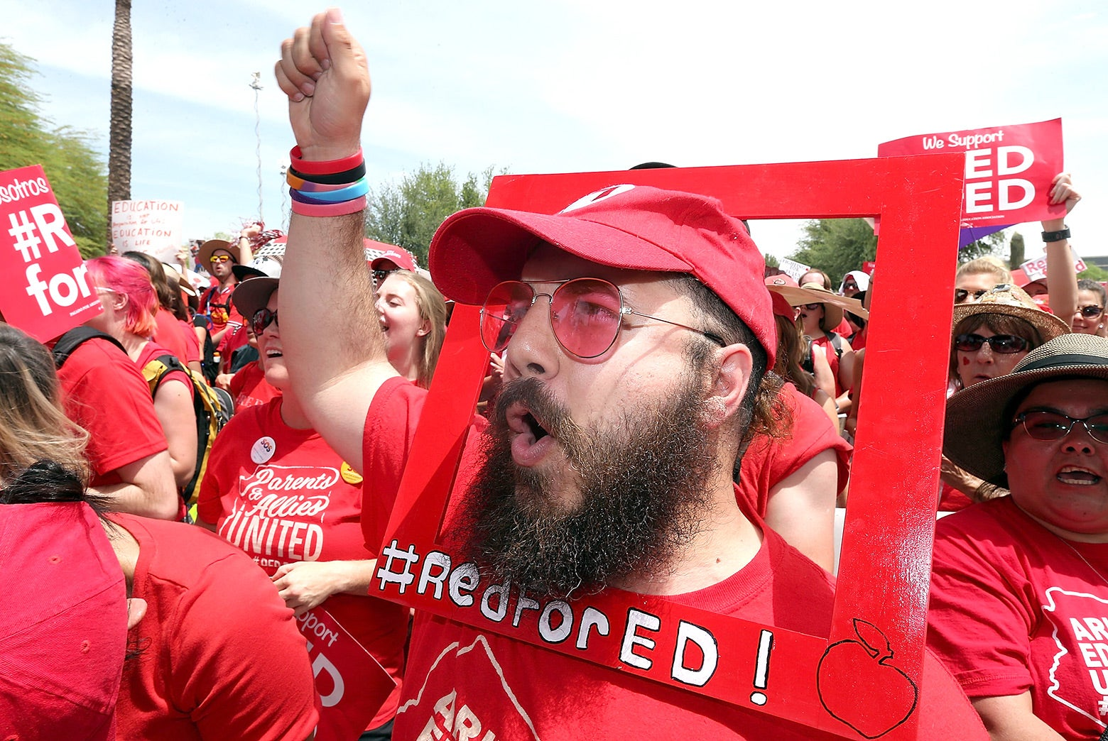 Aude Odeh wears a Red for Ed poster around his face.