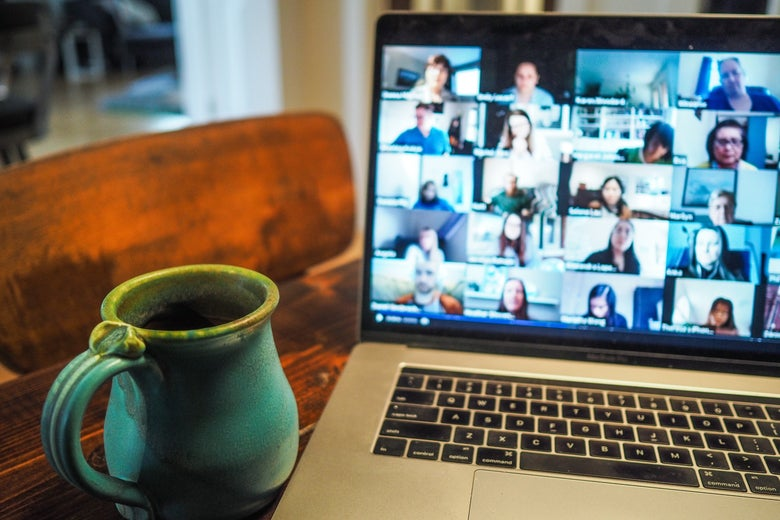 A mug and laptop showing a grid of faces on Zoom sit on a table.