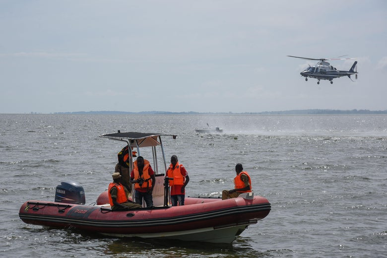 Five men in orange vests look over the waters while standing on a rescue vessel. Overhead, a helicopter hovers.