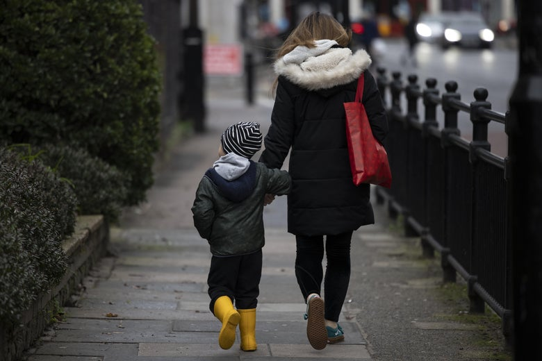 A woman and her son are seen from behind, walking and holding hands on a gated sidewalk.