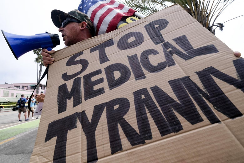 An anti-vaccination protester uses a bullhorn and holds a sign that says STOP MEDICAL TYRANNY and an American flag as he takes part in a rally against COVID-19 vaccine mandates.
