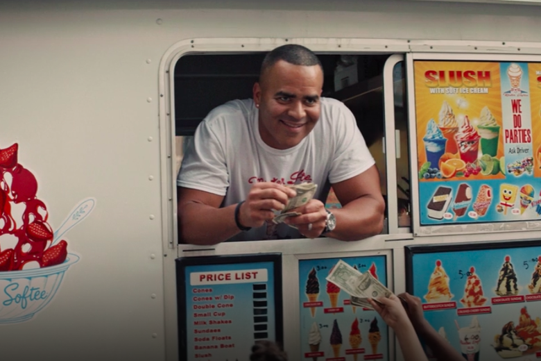 Chris Jackson leans out the window of an ice cream truck, smirking and holding a stack of dollar bills.