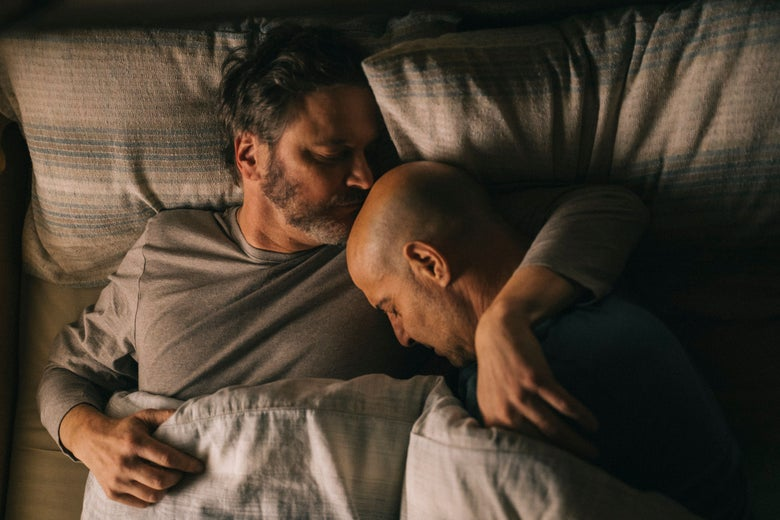 The two men share an embrace while in bed