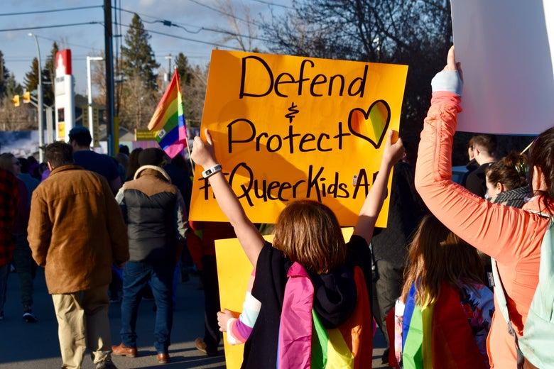 """A young person draped in pride flags marches in a parade carrying a sign reading """"Protect and Defend Queer Kids."""""""