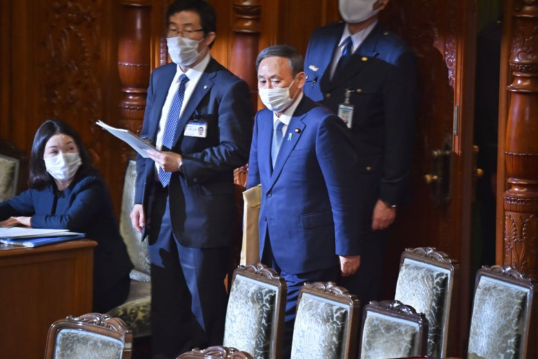 A masked Suga enters parliament surrounded by aides.