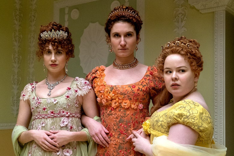 Harriet Cains, Bessie Carter, and Nicola Coughlan wear gowns covered in embroidered flowers and sport oversized, glittering necklaces, earrings, and tiaras. All three have red hair worn up with tight curls; a lock of Penelope's hair cascades down one shoulder.