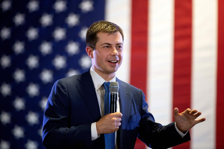 Pete Buttigieg stands in front of an American flag, holding a microphone in his right hand and raising his left.