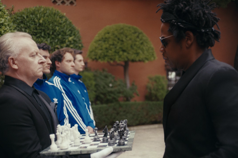 Jay-Z stands in front of a chessboard being held by a man in line with some other men.
