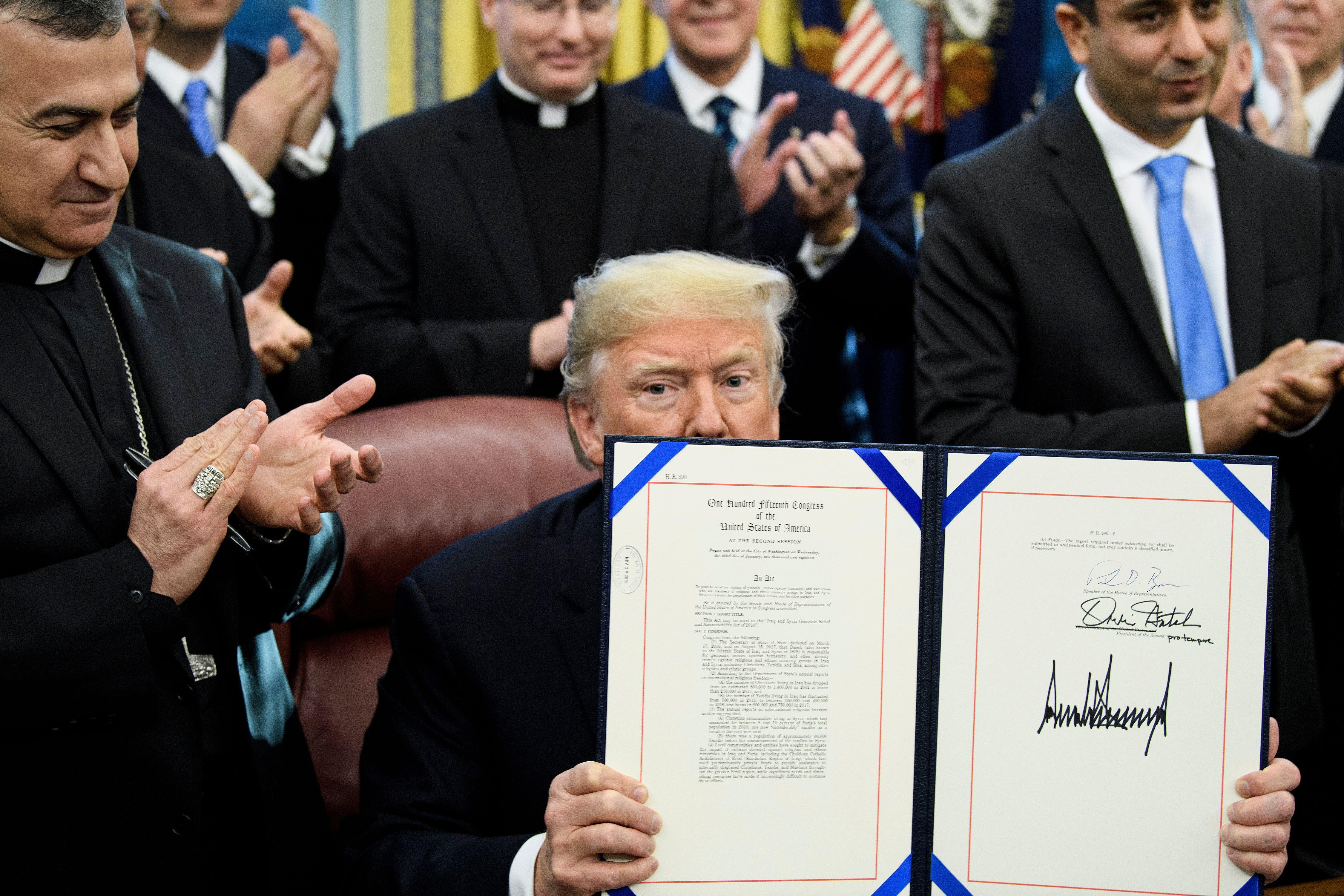 President Donald Trump shows H.R. 390, a bill that activates support for Christians and Yazidis targeted by ISIS, after signing it in the Oval Office on Tuesday.