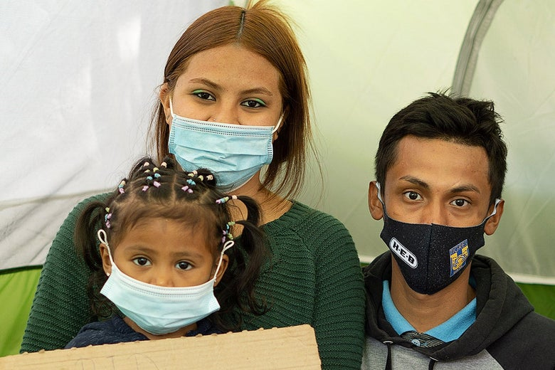 A man, woman, and child, all wearing face masks.