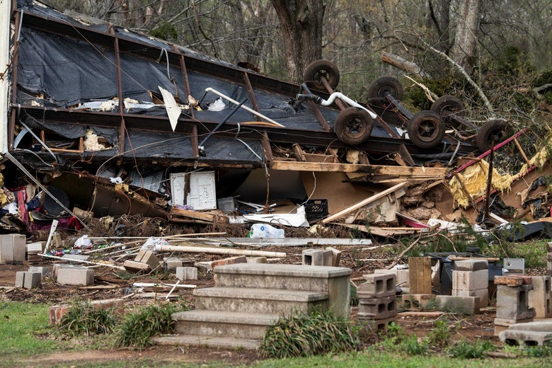 A flipped over mobile home with debris surrounding it