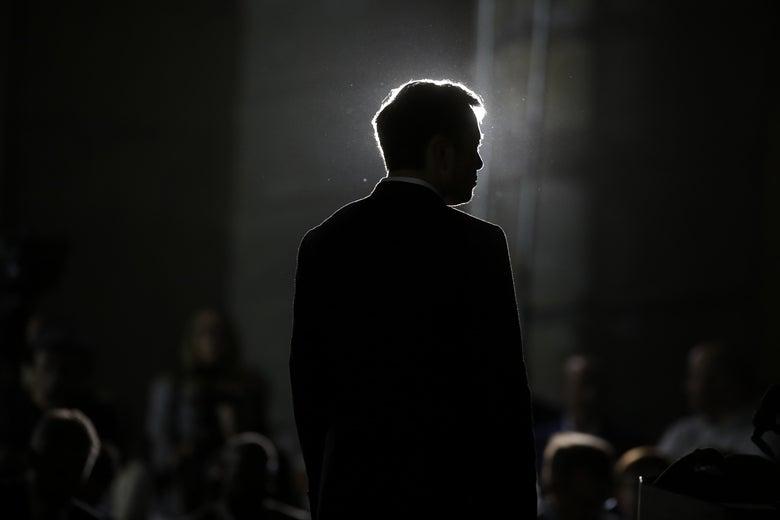 Elon Musk, seen in near-silhouette.