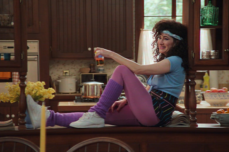 She reclines on the counter, her hair big, her leggings purple, a glass in her hand