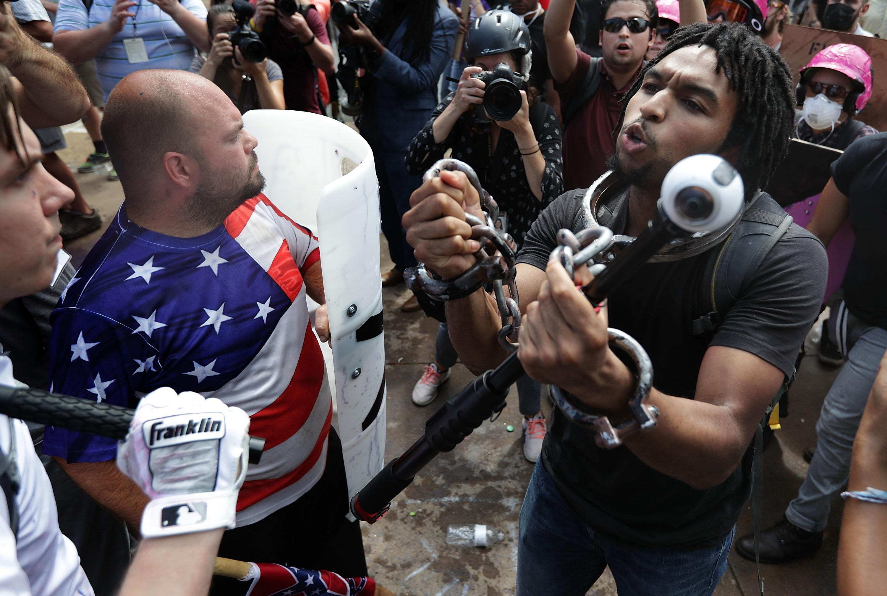 """White nationalists, neo-Nazis and members of the """"alt-right"""" exchange insluts with counterprotesters as they attempt to guard the entrance to Emancipation Park during the Unite the Right rally August 12, 2017 in Charlottesville, Virginia."""
