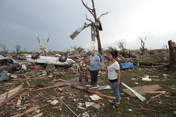 stand in the rubble of his house after a powerful tornado ripped through the area on May 20, 2013 in Moore, Oklahoma.