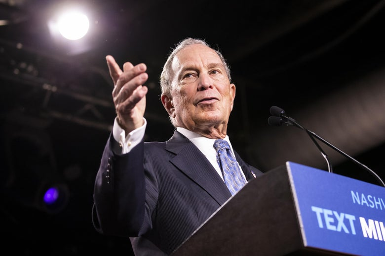 Michael Bloomberg gestures while talking behind a podium that says TEXT MIKE.