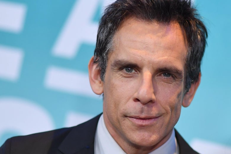 Ben Stiller looks at the camera, wearing a black suit and standing in front of a blue background.