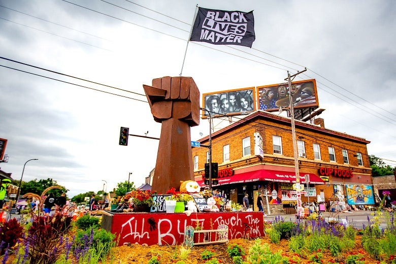 A wooden raised fist statue stands  in the middle of an intersection that has become a memorial.