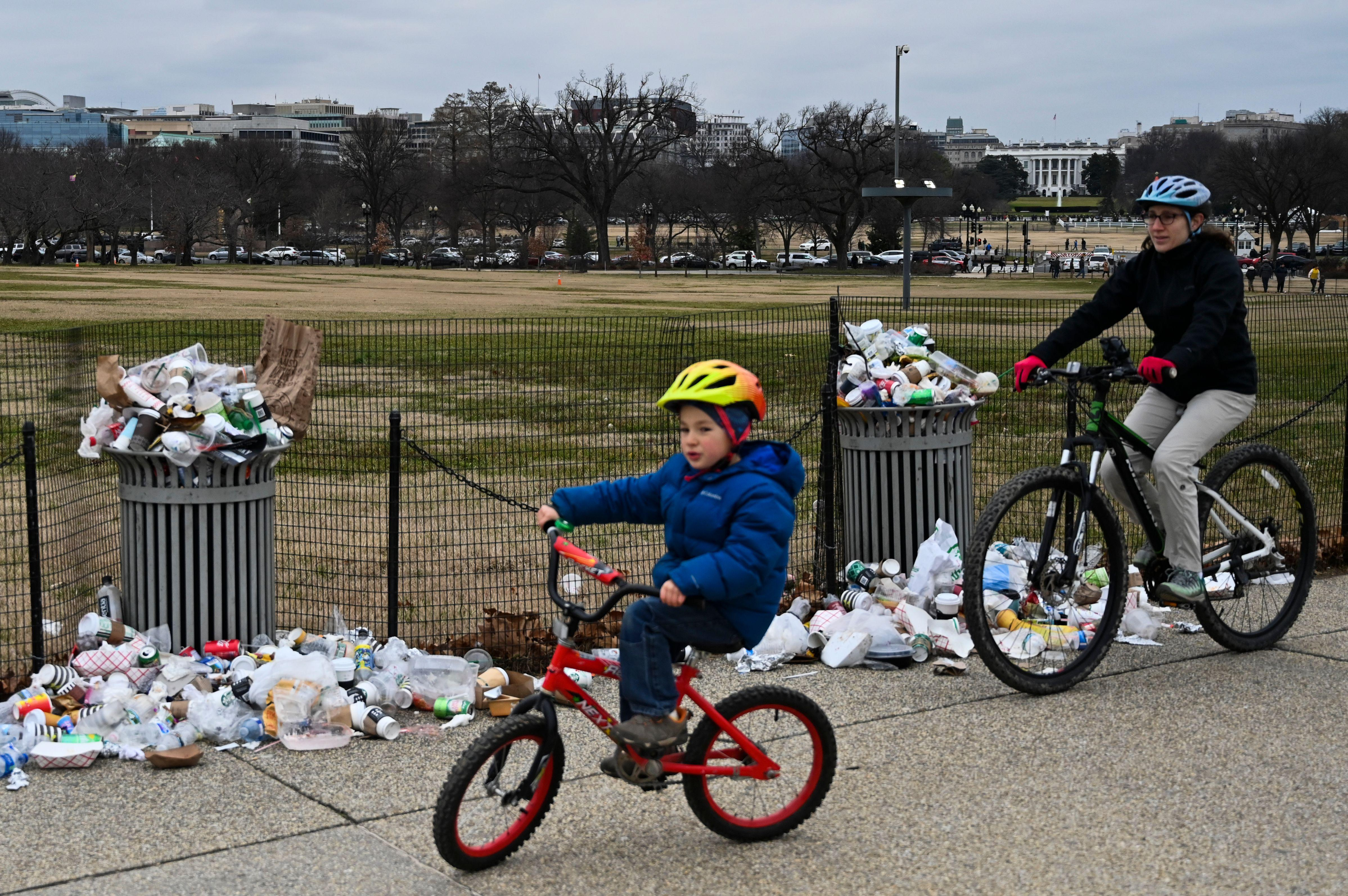 A child and adult on bicycles pass overflowing garbage cans. Behind them, the White House is distantly visible.