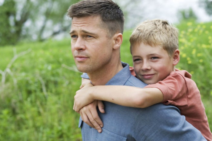 Medium shot of a clean-shaven Brad Pitt carrying a 13 year-old Laramie Eppler on his back in a green field