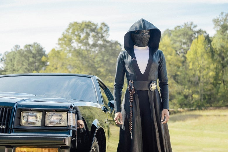 A black-cloaked figure wearing a mask stands next to a car.