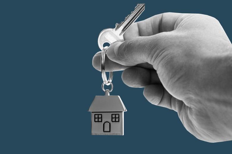 A hand holds a key that includes a keychain shaped like a house.