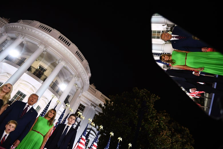 The Trump family stands in front of the White House at night. Their image is reflected in the screen of a teleprompter.