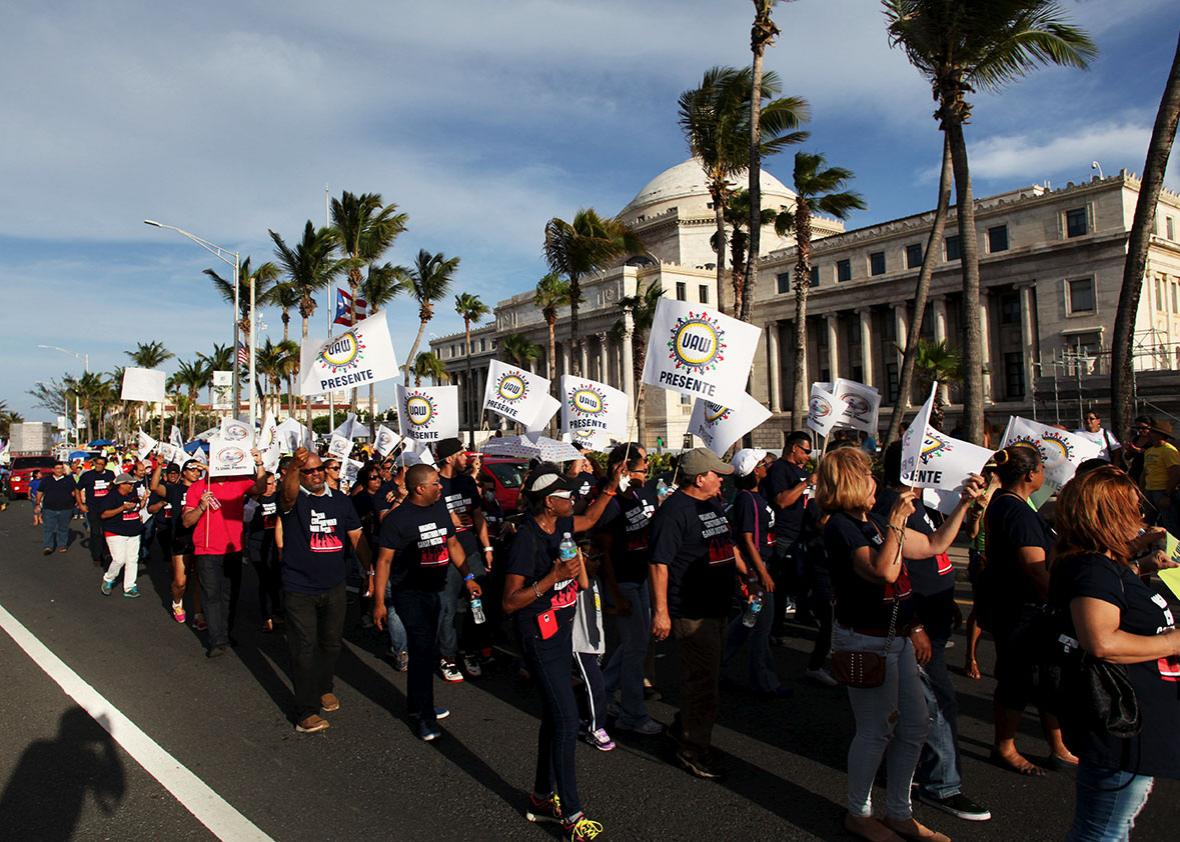 Members of labor unions march past the capitol building during a protest in San Juan September 11, 2015.