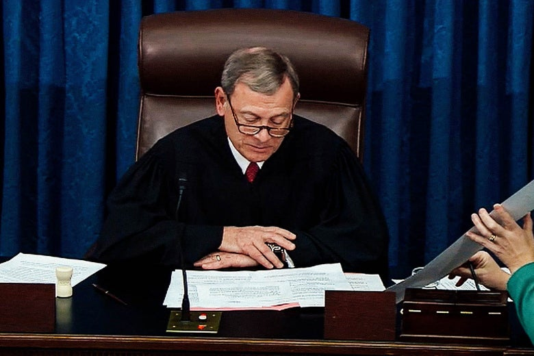 Chief Justice John Roberts at the bench reading a document.