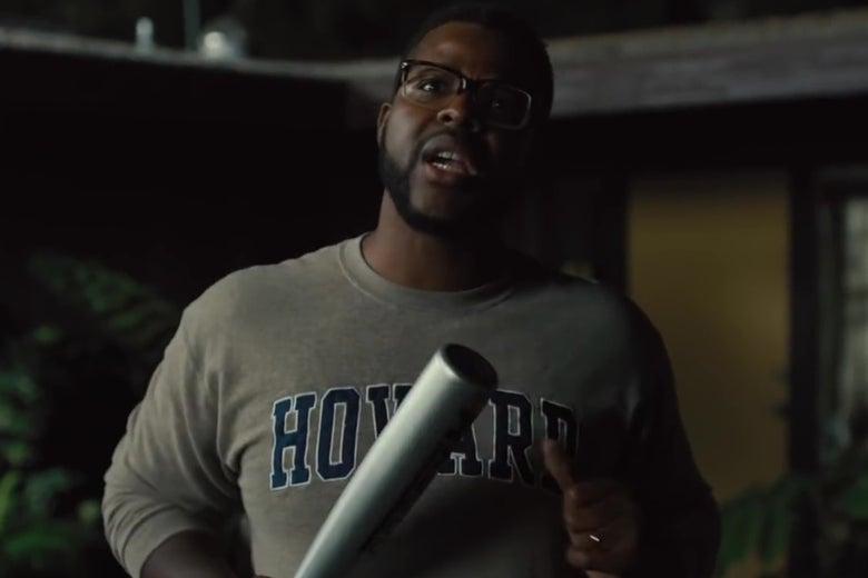 Winston Duke holding a baseball bat.